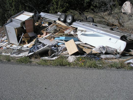 A camper trailer rests where it landed after a rollover