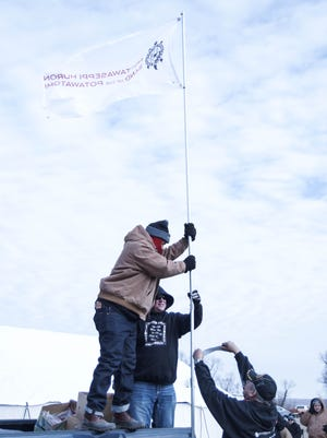Members of the Fulton-based Nottawaseppi Huron Band of Potawatomi plant their flag at the Standing Rock Reservation protests of the Dakota Access Pipeline.