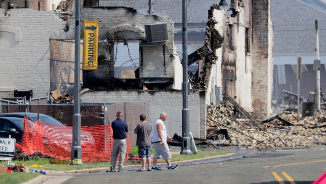 People look at a destroyed building on South Bristol Street just south of West Main Street in Sun Prairie on Wednesday. Emergency crews are investigating after an explosion thought to be caused by a gas line break rocked downtown Sun Prairie. Buildings and businesses along West Main Street have been destroyed or heavily damaged. Firefighter and bar owner Cory Barr died from injuries sustained in the blast.