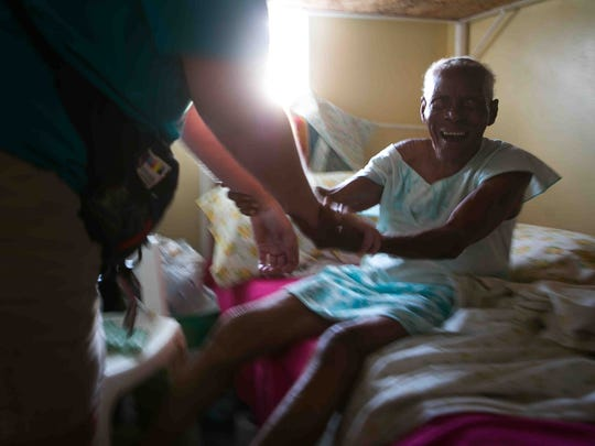 """Ninety-nine-year-old Gwendolyn Magloire smiles as members of the Delaware Medical Relief Team sing """"Happy Birthday"""" to her at a shelter in Portsmouth, Dominica."""
