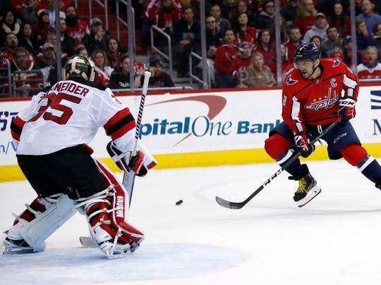 Washington Capitals left wing Alex Ovechkin (8), from Russia, can't handle a pass with New Jersey Devils goaltender Cory Schneider (35) in the net in the second period of an NHL hockey game, Saturday, Dec. 30, 2017, in Washington.