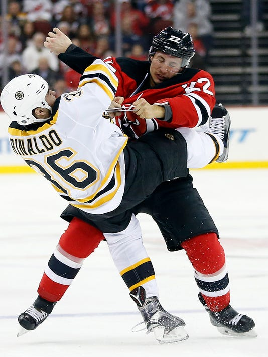 Boston Bruins center Zac Rinaldo (36) is dropped while fighting with New Jersey Devils right wing Jordin Tootoo (22) during the first period of an NHL hockey game, Friday, Jan. 8, 2016, in Newark, N.J. (AP Photo/Julio Cortez)