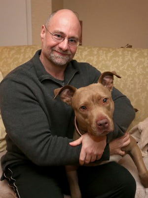 Todd Schisel at his town of Wausau home with his pit bull Nivea.