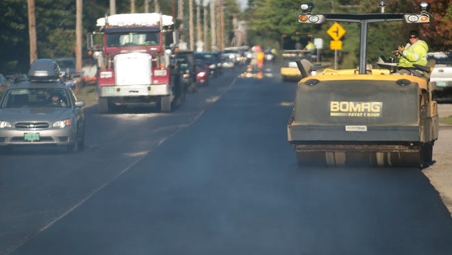 """Paving crews from Pike Industries lay down a """"band aid"""" of fresh pavement along Vermont 15 east of Sandhill Road in Essex in 2012. Under the new budget, paving between town and village will be consolidated."""