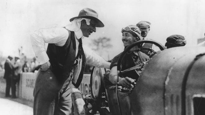 Driver Jules Goux, smiling, talks with Charles Faroux, a French sportsman who served as unofficial team manager for Peugeot during the 1913 Indianapolis 500.