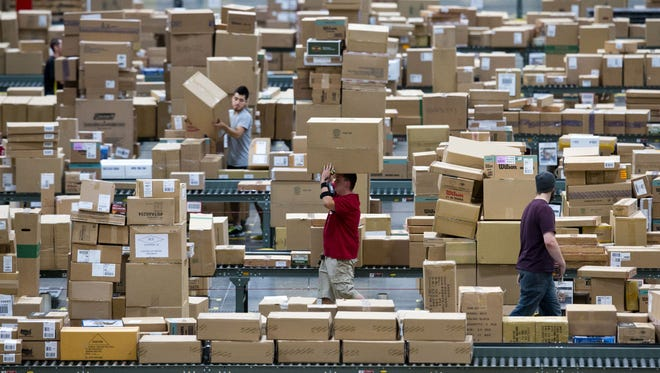 Dustin Parker (center) of El Mirage loads pallets shipped from Dick's Sporting Goods' distribution center in Goodyear in 2013.