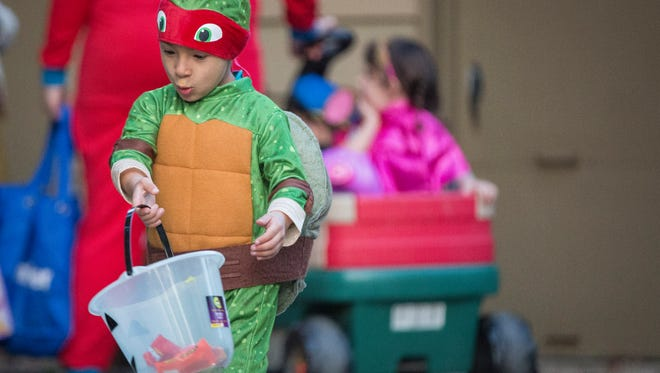 Hundreds of children roam through Muncie neighborhoods collecting candy during trick-or-treating hours Monday evening for Halloween.