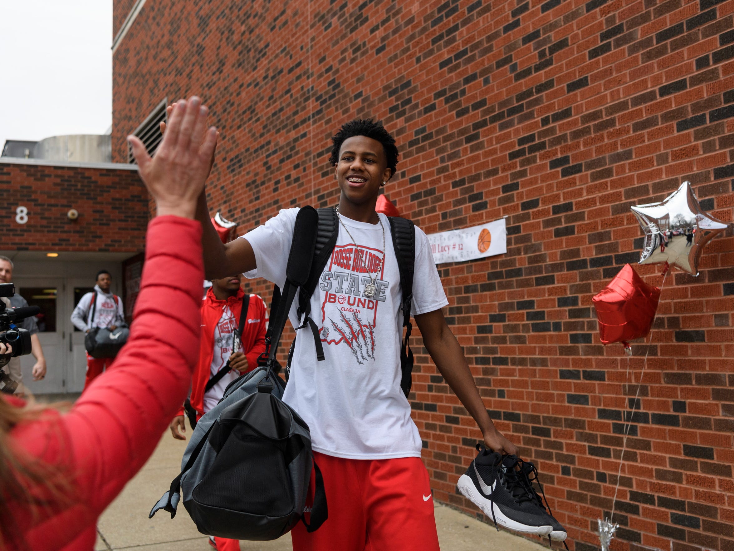 Kiyron Powell (52) receives a high-five as he walks to the bus during a state championship send-off for the basketball team at Bosse High School in Evansville, Ind., Friday, March 23, 2018. The team will compete in tomorrow's Class 3A State Championship game at Bankers Life Fieldhouse in Indianapolis.