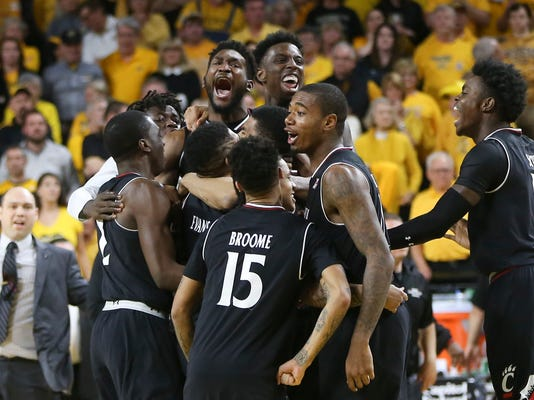 Cincinnati players celebrate after winning an NCAA college basketball game against Wichita State in the American Athletic Conference tournament Sunday, March 4, 2018, in Wichita, Kan. (Travis Heying/The Wichita Eagle via AP)