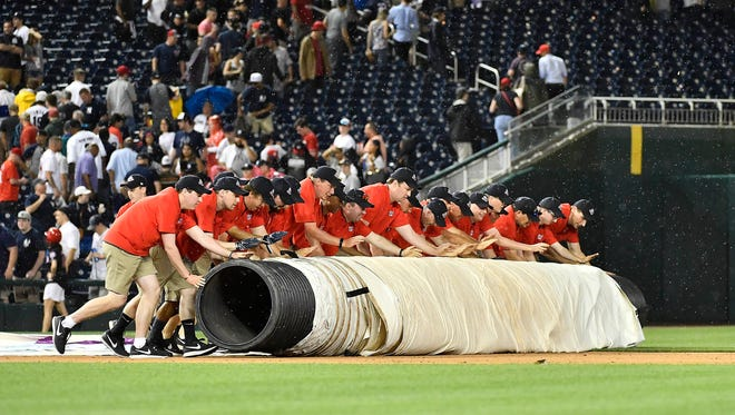 Washington Nationals grounds crew roll out the tarp during a rain delay during the sixth inning of a game between the Washington Nationals and the New York Yankees at Nationals Park.