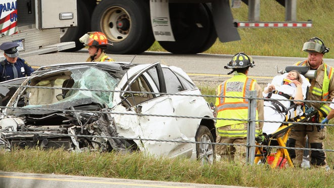 Michigan State Police Troopers join Livingston County EMS Ambulance personnel and Brighton Area firefighters aS they work the scene of a rollover accident on US-23 just north of Spencer Road.Photo by ALAN WARD / DAILY PRESS & ARGUS