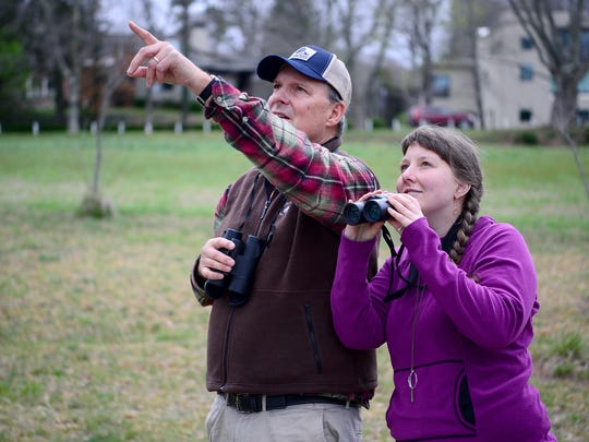 Josh Henninger points out a bird for his daughter, Trudie, as they take a bird walk with the Elisha Mitchell Audubon Society near the Beaver Lake Bird Sanctuary on Saturday, April 1, 2017.