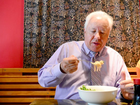Carl Twigg prepares for a big bite of his lunch at Doc Chey's on Biltmore Avenue on Thursday, Aug. 3, 2017.