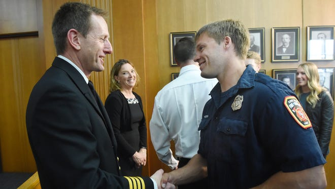 Brad Goodroad (left), Sioux Falls Fire Chief finalist, is congratulated by firefighter Jeremy Hill after a press conference on Friday at City Hall.