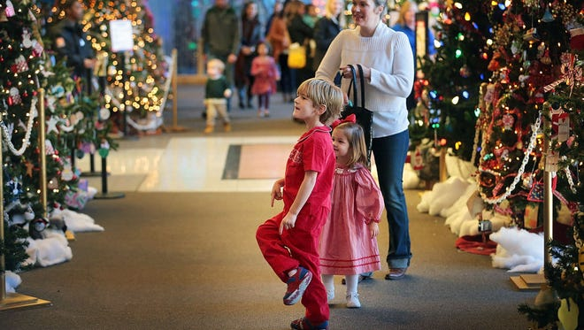 Families wander through the Festival of Trees, part of the Pink Palace's Enchanted Forest. In its 15th year at the Pink Palace, the animatronic exhibit features 89 figures, a gingerbread village, and Santa.