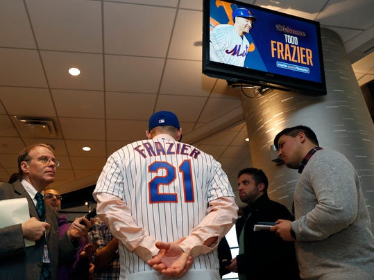 Journalists interview newly-signed New York Mets third baseman Todd Frazier after the former New York Yankees player signed with the team, Wednesday, Feb. 7, 2018, in New York. (AP Photo/Kathy Willens)