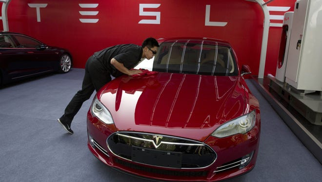 A worker cleans a Tesla Model S sedan before an event in Beijing, China, Tuesday, April 22, 2014.