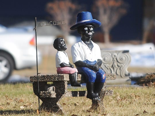 Statues of black caricatures near a welcome sign sit on the front lawn of a residence along South Main Street in Fond du Lac.