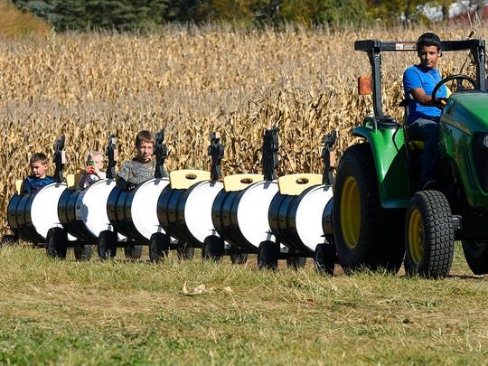 Children take a ride on the cow train around the field at the A and G Corn Maze Sunday, Oct. 11, 2015 in St. Joseph.