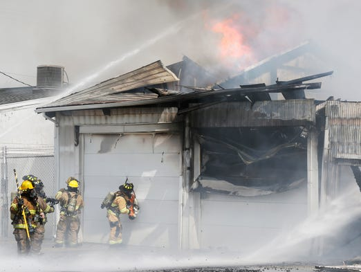 Firefighters saw through a garage door to access flames as they battle a structure fire Thursday, April 24, 2014, in the 800 block of S. Earl Avenue in Lafayette.
