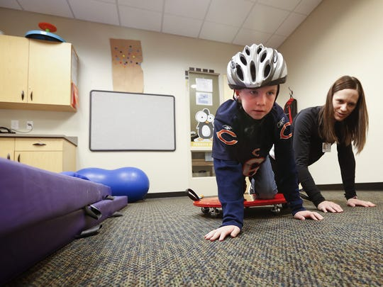 Treyner Ramus, 8, who suffers from a brain injury and disruptive mood disorder works with occupational therapist Emily Monahan at ChildServe in Johnston Thursday, Dec. 3, 2015.