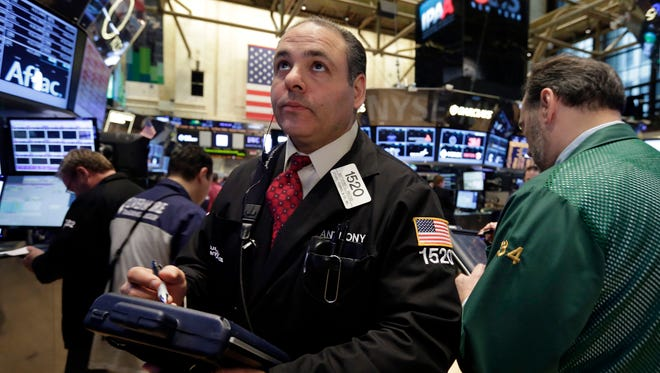 In this April 7, 2014 file photo, trader Anthony Riccio, works on the floor of the New York Stock Exchange.