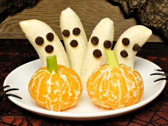 """Healthy Halloween treats could include these banana ghosts with raisins for eyes and orange  (and celery stick) """"pumpkins,""""."""