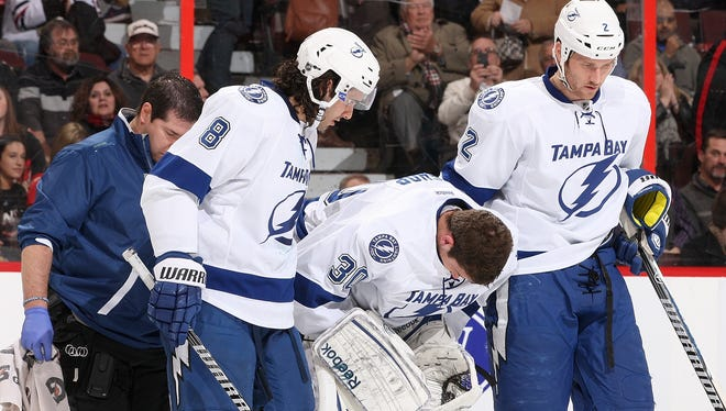 Goalie Ben Bishop is helped off the ice by teammates after taking a teammate's skate to the back of his head.