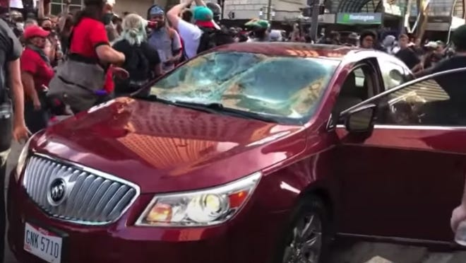 This image from a video shows Eldon Hawkins' damaged car surrounded by protesters Downtown on May 31.