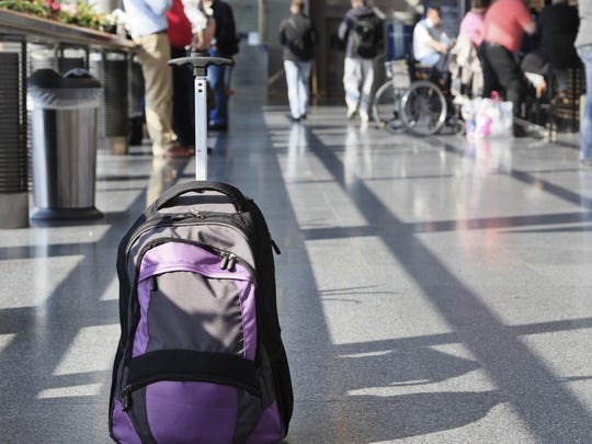 A backpack sits unattended near an airport check-in line.