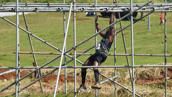 In this file photo, a participants climbs through a pipe structure in the KONQER Obstacle Course Race.