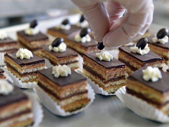 Pastry chef Alejandra Mamud tops off pieces of opera