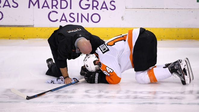 Flyers center Sean Couturier kneels on the ice after suffering an injury in the second period of a victory over the Panthers on Tuesday.
