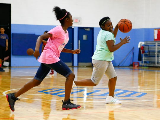 Sisters Autumn (12, left)) and Aidyn Williams, 11, play basketball in the Fraim Boys and Girls Club in Wilmington Monday after 8 p.m.