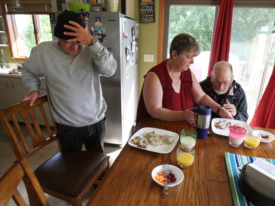 In this Sept. 28, 2017 photo, Judy Willis serves lunch to two of her foster care residents in her northwest Rochester, Minn. Willis and her husband have set up their home with space for several foster care adults.
