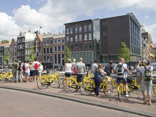 Tourists on a bike tour wait in front of the Anne Frank House Museum in Amsterdam.
