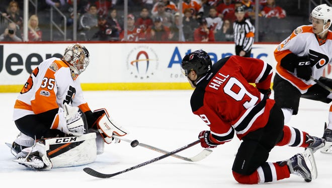 Philadelphia Flyers goalie Steve Mason (35) stops a shot by New Jersey Devils left wing Taylor Hall (9) during the second period of an NHL hockey game, Tuesday, April 4, 2017, in Newark, N.J. (AP Photo/Julio Cortez)
