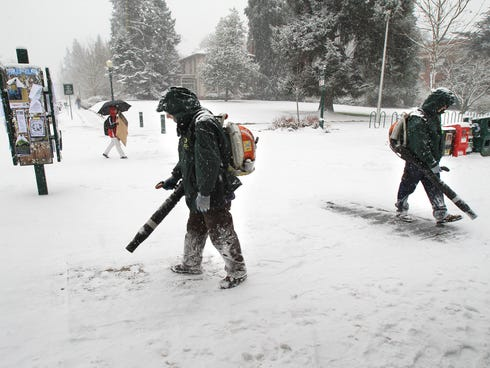 Snow blowers work on the campus of the University of Oregon in Eugene, Ore. on Dec. 6.