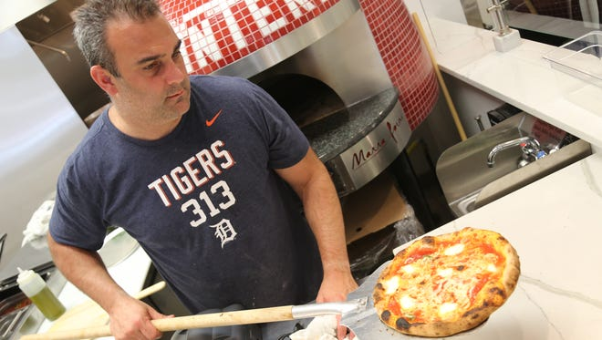 Ed Barbieri III pulls a margherita pizza out of the oven at La Lanterna, which debuts in Detroit's Capitol Park Wednesday, April 13, 2017.