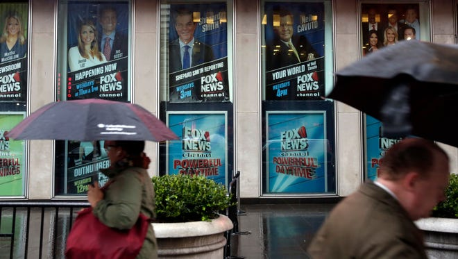 Pedestrians walk by the Fox television studios, where a poster of Bill O'Reilly has been removed, April 20, 2017, in New York. Fox dismissed O'Reilly the previous day.