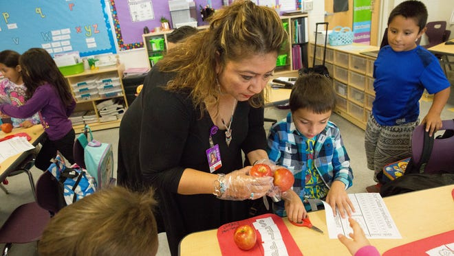 Eloisa Solis, the principle at Valley View Elementary School, hands out Braeburn apples to students in Courtney Degler's first-grade class on Tuesday, October 24, 2017. Students at Valley View and around the district are participating in Apple Crunch week, a program aimed at teaching students about healthy foods that ties into all the subjects they will be learning this week, from math to literature.