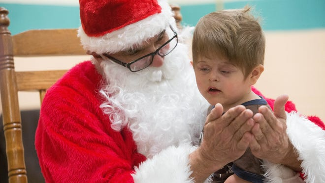 Santa Claus signs asking Avery Kessel, 2, what kind of book he would like for Christmas, during the Las Cruces New Mexico School for the Deaf Preschool Winter Celebration Dinner Party. Monday Dec.4, 2017 at Mesilla Elementary School.