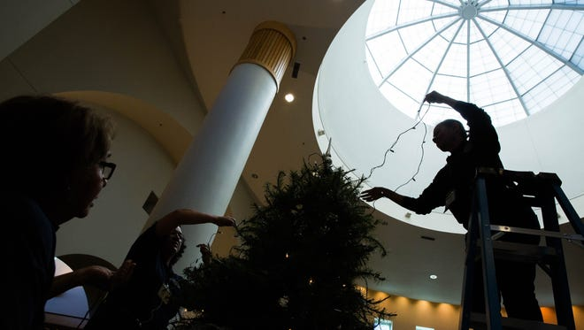 Olga Herrera, right, along with Graciela Chavez, center, and Esperanza Peña, all building attendants with the Doña Ana County Government Center, wrap a tree with lights on the second floor of the lobby Wednesday Dec. 13, 2017.