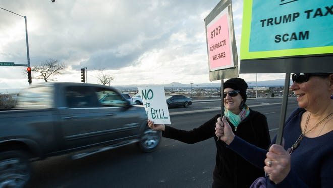 Mary Martinez White, left, and Jennifer, who did not provide her last name, hold up signs protesting a proposed federal tax bill Monday Dec. 18, 2017 on the corner of Telshor Boulevard and Foothills Drive. The protest, put on by Indivisible Las Cruces, saw more than 15 protesters spread out on the four corners of the intersection, waving signs and cheering when cars would honk.