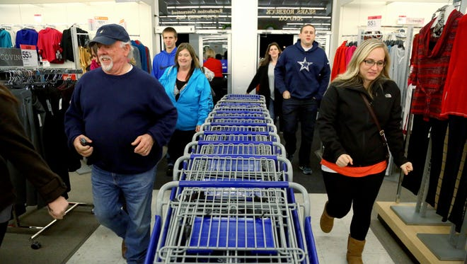 Shoppers rush through the doors at Sears in Paris, Texas, on Nov. 28, 2013, looking for deals on electronics, tools and appliances.