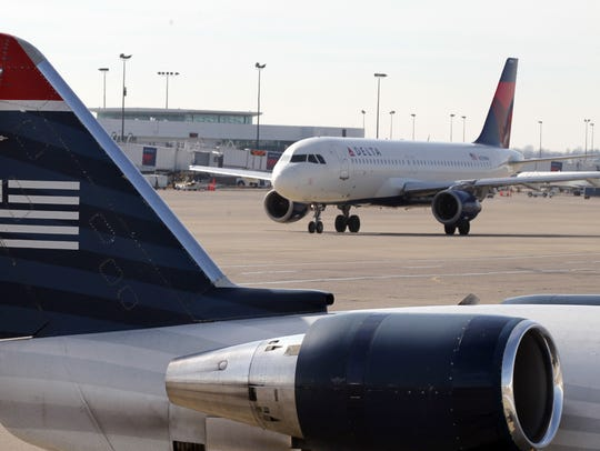 A Delta jet taxies toward the tail of a U.S. Airways