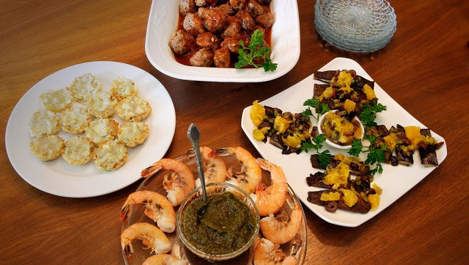 Array of crowd-pleasing appetizers (clockwise from left): Blue cheese and Pear Tartlets, Party-Perfect Meatballs, Portobello Carpaccio with Orange-Kalamata Tapenade, Shrimp with Sauce Verte.