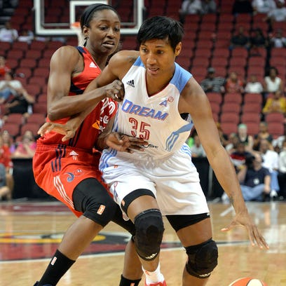 Atlanta's Angel McCoughtry, right, attempts to drive