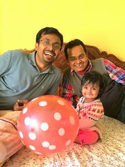 Naveen and Praveen Sinha, right, play with Naveen's