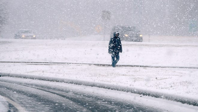 A pedestrian walks during heavy snowfall along Garland Groh Blvd. in Hagerstown, Md., Tuesday, March 20, 2018.